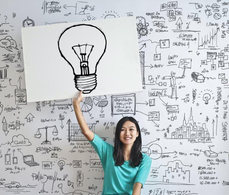 Dame sitzt vor bemalten Whiteboard und hält Plakat mit gezeichneter Glühbirne in der Hand